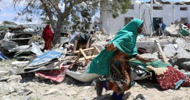 A woman runs past the debris at the site of a blast in the district council office of Hawlwadag in Mogadishu, Somalia. Photograph: Feisal Omar/Reuters